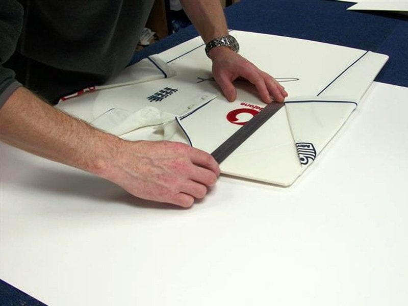 Carefully measuring the sleeve-line on a signed Freddie Flintoff shirt