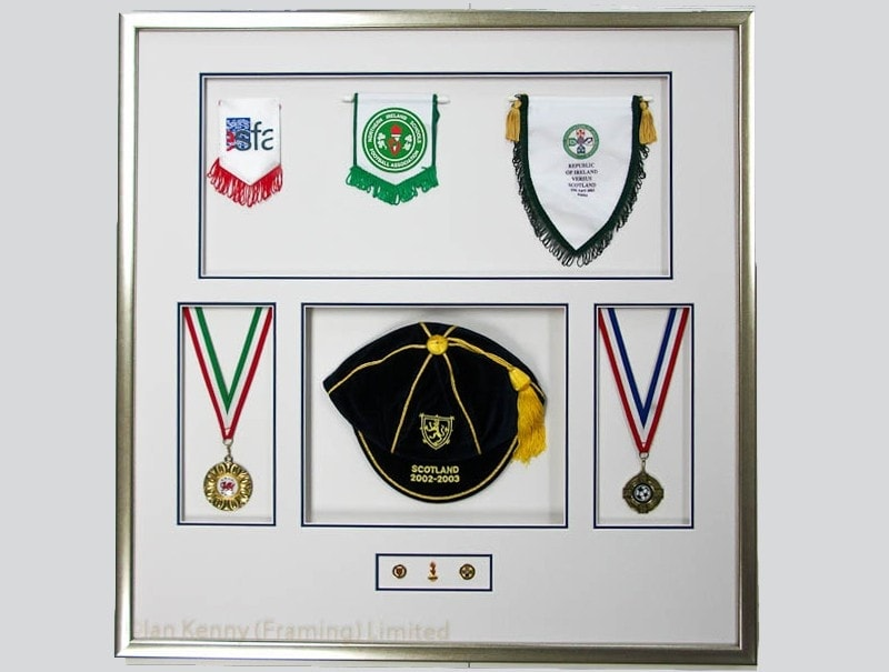 Pennants, medals, badges and an International Cap in a deep frame